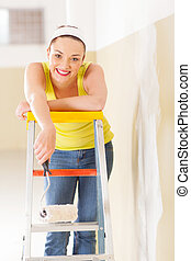 happy young woman standing on ladder