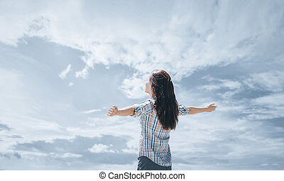 Happy young woman standing with raised arms in front of cloudy sky in summer.
