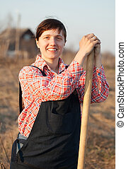 woman standing with spade in rural - Happy young woman ...