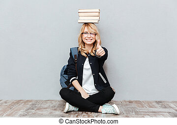 Happy young woman student holding books on head.