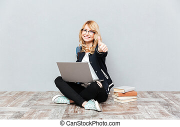 Happy young woman student using laptop computer.