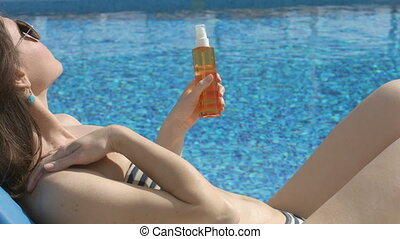 Happy young woman suntanning, applying sunscreen to protect skin