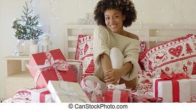 Happy young woman surrounded by Christmas gifts - Happy...