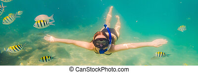 Happy young woman swimming underwater in the tropical ocean BANNER, LONG FORMAT