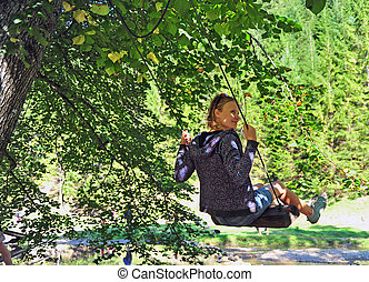 Happy young woman swinging in the park