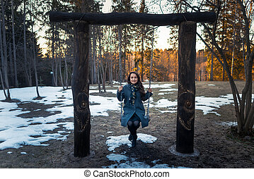 Happy young woman swinging on a swing