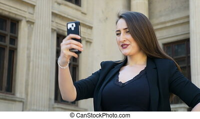 Happy young woman taking a photo of herself and posting it on social media