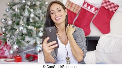 Happy young woman taking a selfie at Christmas
