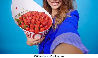 Young woman taking photo of herself with a bouquet of strawberries