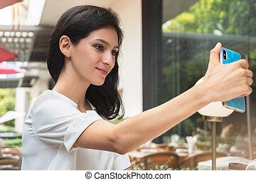 Happy young woman taking selfie in a restaurant terrace