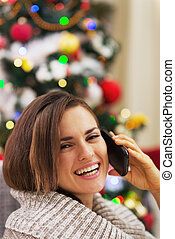 Happy young woman talking cell phone near christmas tree