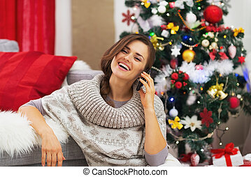 Happy young woman talking mobile phone near christmas tree