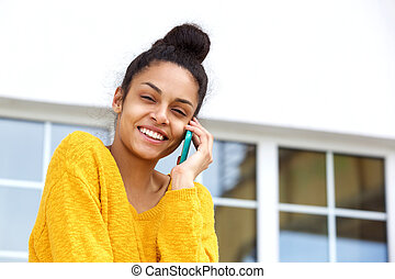 Happy young woman talking on cell phone