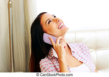 Happy young woman talking on the phone at home