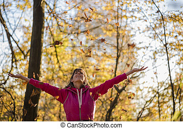Happy young woman throwing leaves in the air