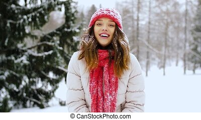 happy young woman throwing snow in winter forest - people,...