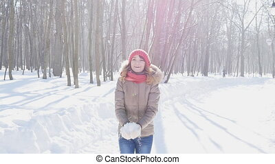 Happy young woman throws snow in park, slowmotion