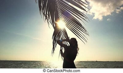 Happy young woman touching palm leaf and the sun. Woman enjoying bright tropical sun with lens flare effects in slow motion.