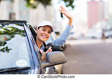 happy young woman touring in the city by car