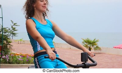 happy young woman training on gym apparatus, sea in background
