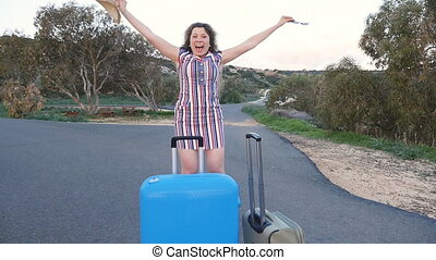 Happy young woman traveler with suitcase dancing