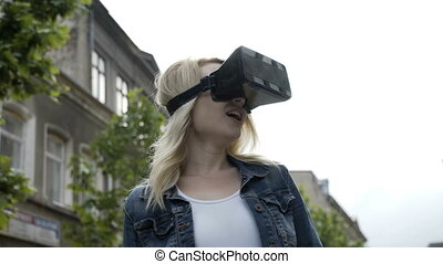 Happy young woman trying a virtual reality vr set feeling amazed