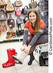 Happy young woman trying water boots in dressing room