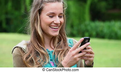Happy young woman typing on her cellphone