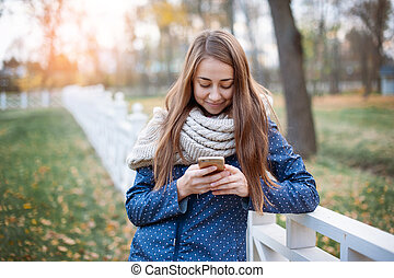 Happy young woman using a smart phone during the walk in autumn city park.