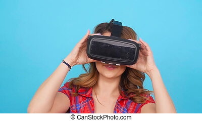 Happy young woman using a virtual reality headset in blue...