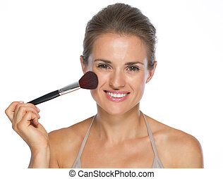 Happy young woman using brush