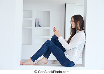young woman using cellphone at home