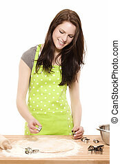 happy young woman using christmas molds on dough in front of white background