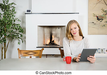 Happy Young Woman Using Digital Tablet At Home