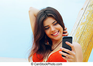 Happy young woman using her smartphone on the beach