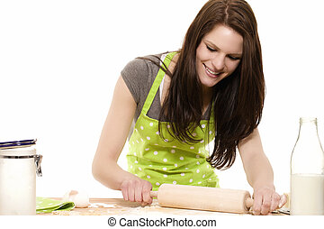 happy young woman using rolling pin on dough with white background