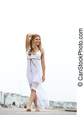 Happy young woman walking barefoot outdoors