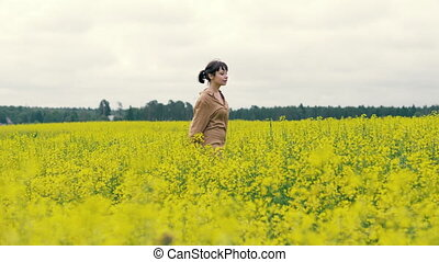 Happy young woman walking in a blooming field on a summer day