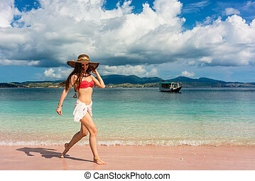 Happy young woman walking through shallow sea water on the beach