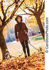 happy young woman walking with dogs outd