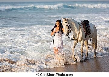 happy young woman walking with horse on beach