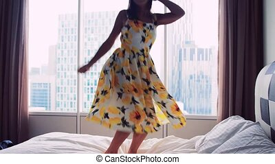Happy young woman wearing beautiful dress dances jumps on bed at home, slow motion. 3840x2160