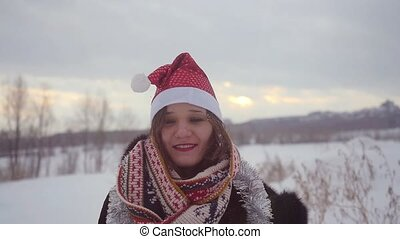 Happy young woman wearing christmas hat having fun outdoors throwing snow in winter snowy nature in slow motion.