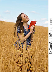 woman with a book in cereals field