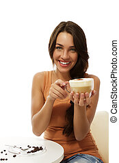 happy young woman with a cappuccino coffee sitting at a table on white background