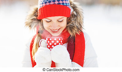 happy young woman with a cup of hot tea in winter walk ...