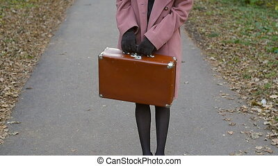 Young woman with a suitcase in an autumn park