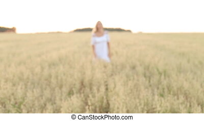 Happy, young woman with a toothy smile running across the wheat field