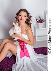 happy young woman with a white rabbit in the studio