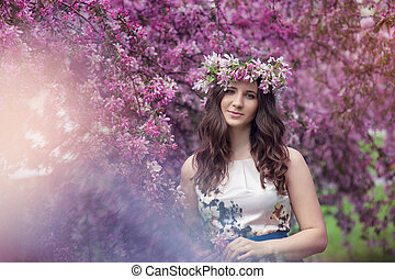 happy young woman with a wreath on his head in the blossoming spring garden